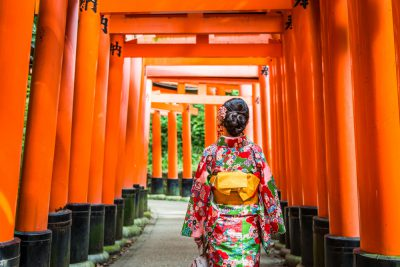Women in kimono stand at Red Torii gates in Fushimi Inari shrine, one of famous landmarks in Kyoto, Japan